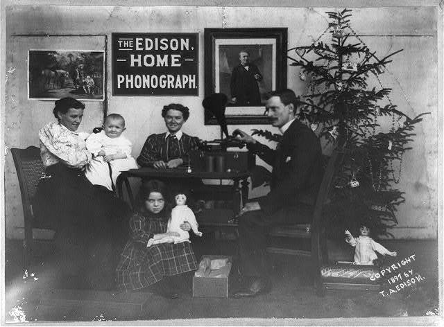 [Man, two women and two children listening to phonograph--Girl is holding doll and another doll is under Christmas tree--There is a sign on the wall, The Edison Home Phonograph, and a portrait of Edison]