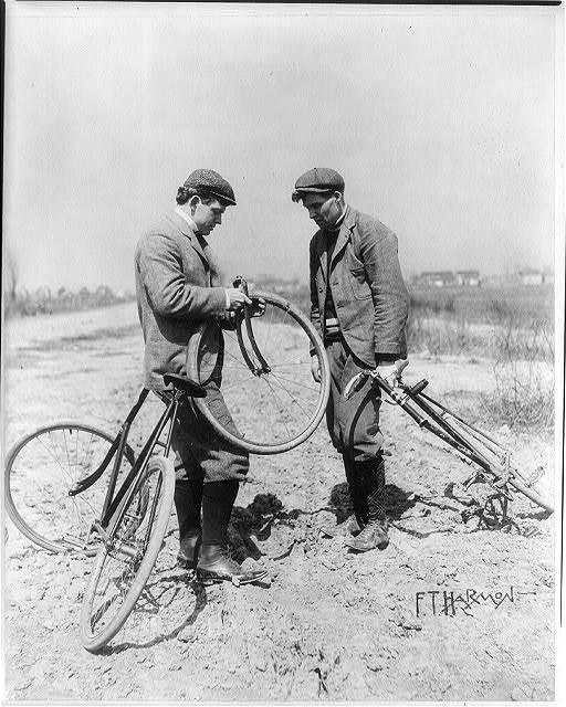 Two men looking at broken bicycle wheel [sic]