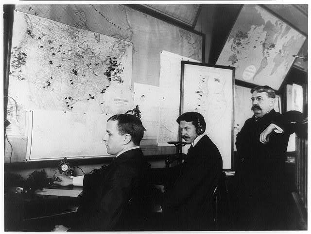 E.C. Heasley, Jules A. Rodier and Maj. Montgomery in the telegraph room in the White House, set up to receive news of the Spanish-American War