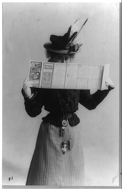 [Edna Wallace Hopper, three-quarter length portrait, standing, facing right, looking over schedule for Chicago & Alton Railroad]