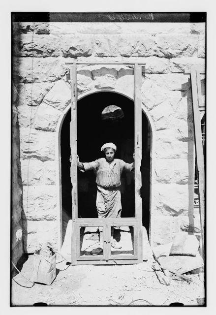 [Man with wooden frame standing in doorway]