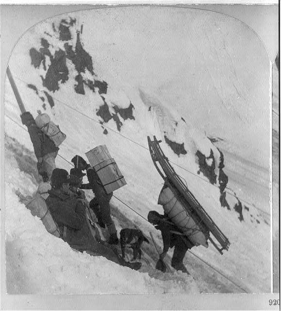 [Miners bound for the Klondike gold fields: close-up of men with heavy packs near summit of Chilcoot Pass]