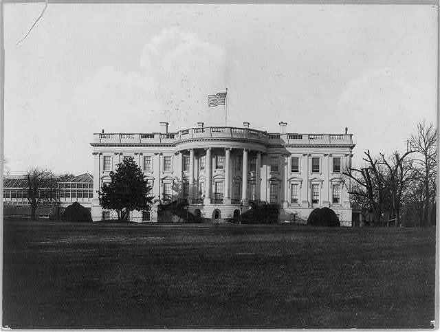 [The White House, Washington, D.C., south facade, with large conservatory wing at left and American flag flying above]