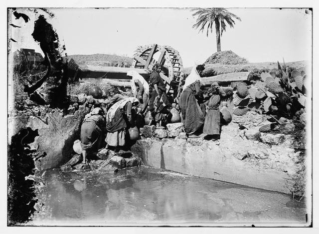 [Women and children with jars getting water from stream next to irrigation wheel]