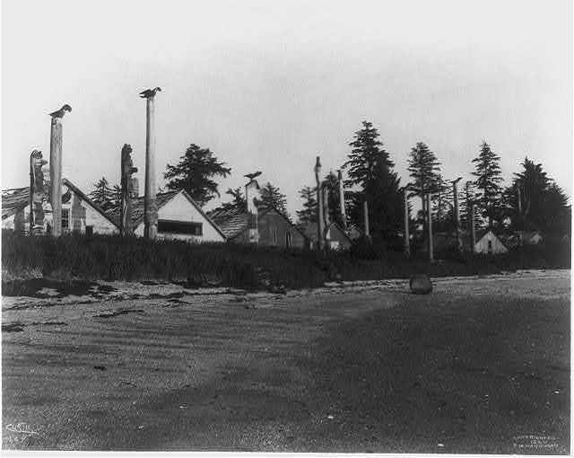 [13 totem poles in front of houses in Alaska or the Aleutian Islands]
