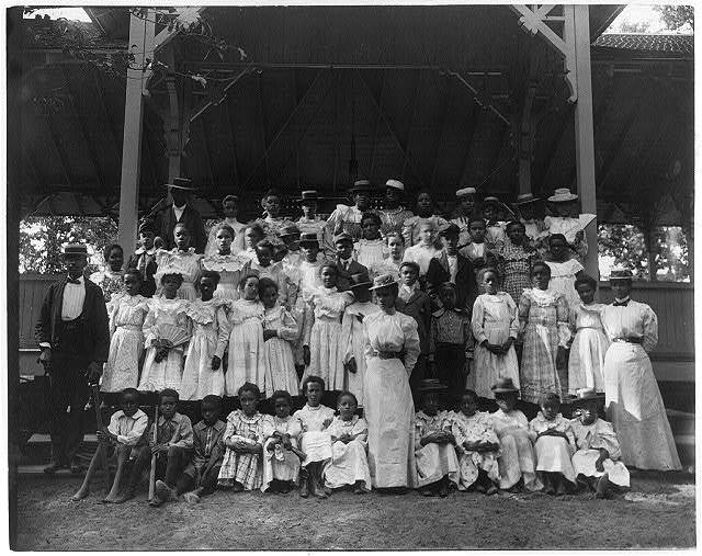 [African American children with a few adults in a pavilion]