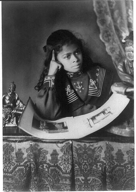 [African American girl, half-length portrait, with right hand to cheek, with illustrated book on table]