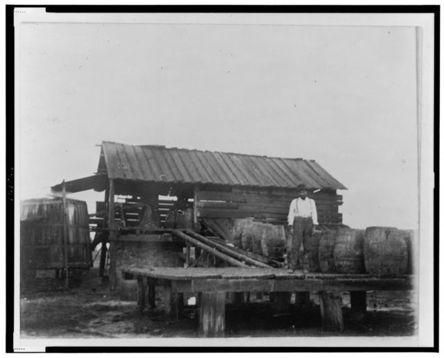 [African American man standing on platform or loading dock with large barrels and a ramp to a structure in the background with a large vat or silo, in Georgia]