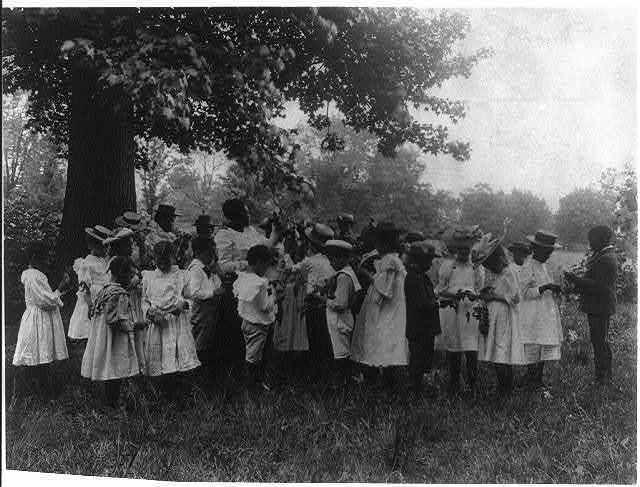 [African American school children and teacher, studying leaves out of doors]