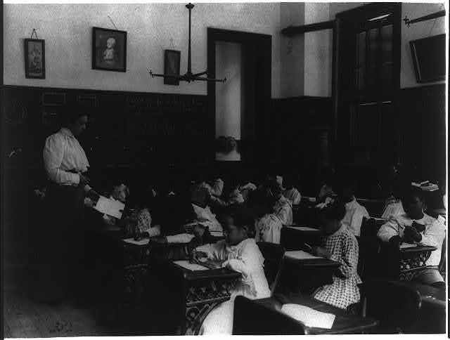 [African American school children at work on a craft project]