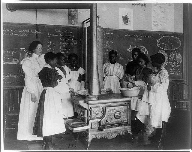 [African American schoolgirls with teacher, learning to cook on a wood stove in classroom]