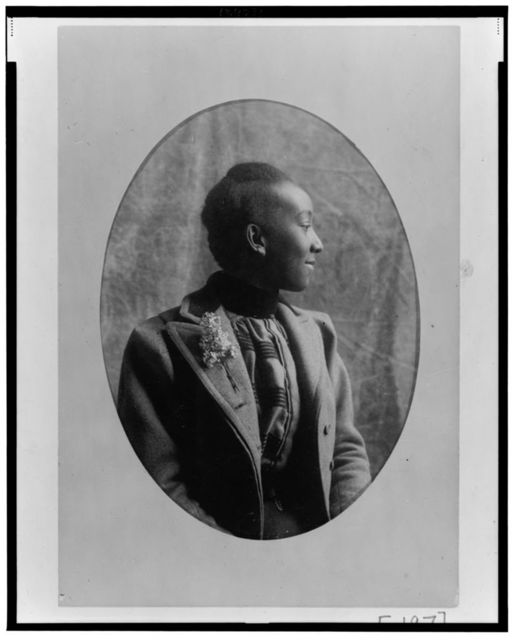 [African American woman, half-length portrait, seated, right profile, wearing coat]