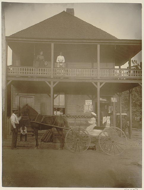[African Americans and horse-drawn wagon in front of country store, two women stand on balcony]