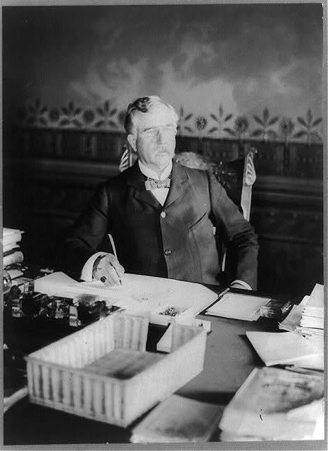 [Alfred Elliott Bates, Paymaster General, half-length portrait, seated at desk, facing right]