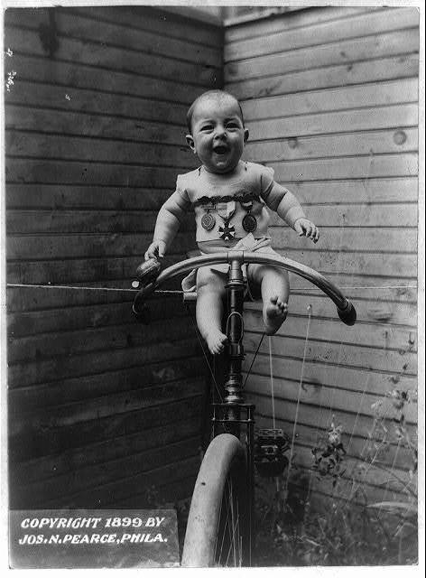 [Baby with sports medals perched on bicycle held upright by rope]