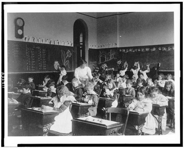 [Children modeling clay at desks and drawing on blackboard in Washington, D.C. classroom]