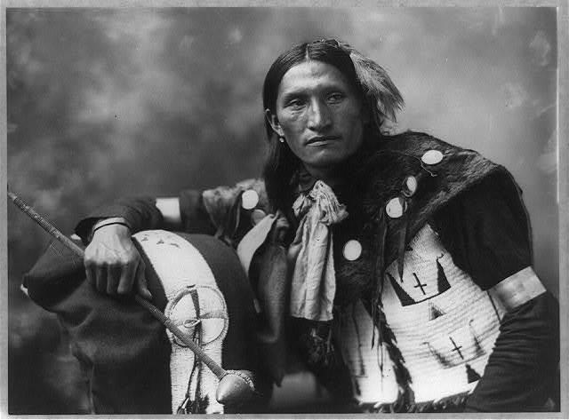 [Eddie Plenty Holes, a Sioux Indian, half-length portrait, facing front, holding tomahawk]
