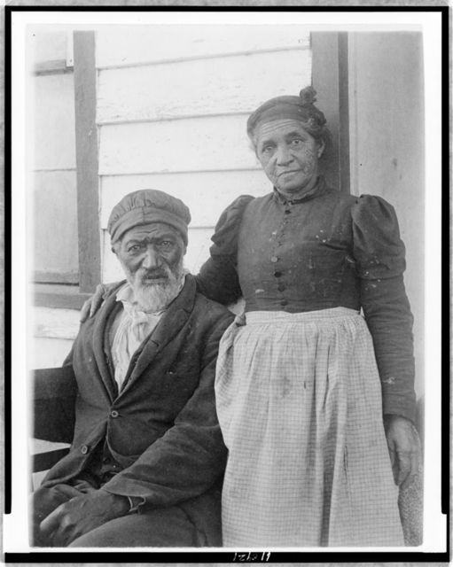[Elderly African American couple posed outside of building, near Hampton Institute, Hampton, Va.]