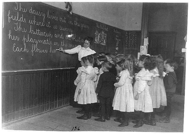 [Elementary school children standing and watching teacher write at blackboard, Washington, D.C.]