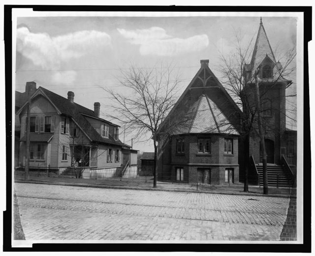 [Exterior view of church and house on cobblestone street]