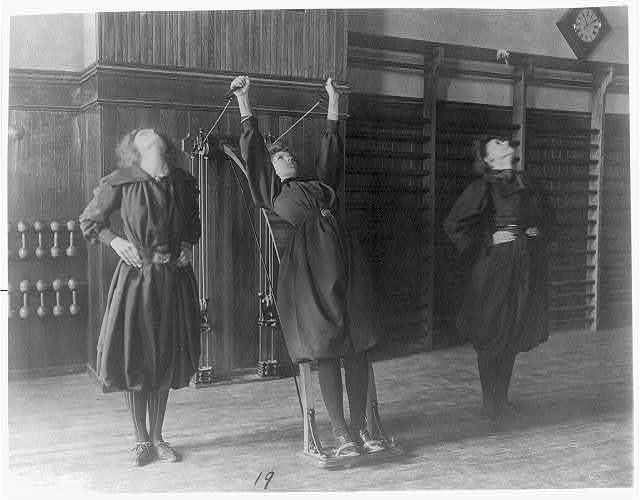 [Female students exercising, one with a wall-mounted device using ropes and pulleys, Western High School, Washington, D.C.]