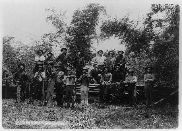 [Group of seventeen American soldiers posed, 2 with violins, 1 with harp, Philippine Islands]