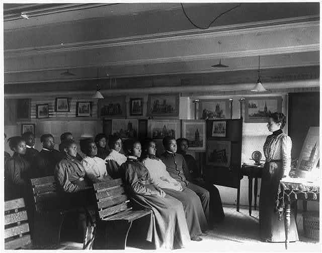 """[Hampton Institute, Hampton, Va., 1899 - male and female students in Geography class """"studying the cathedral towns,"""" by studying artist's renderings of the famous European cathedrals]"""