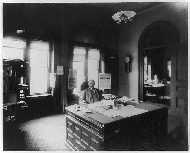 [Henry A. Rucker, internal revenue collector, Atlanta, Georgia, seated at large desk in office]