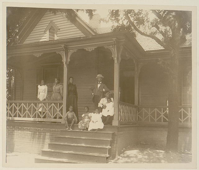 [Home of an African American lawyer, Atlanta, Georgia, with men, women, and children posed on porch of house]