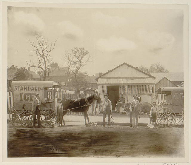 [Horse-drawn ice wagon and several persons, two with blocks of ice, standing in street in front of residence]