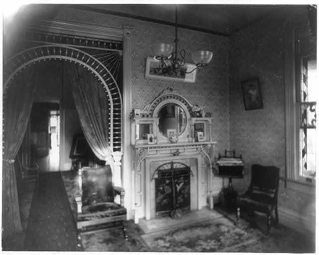 [Interior view of room showing chandelier, decorative arch, fireplace, and furniture]