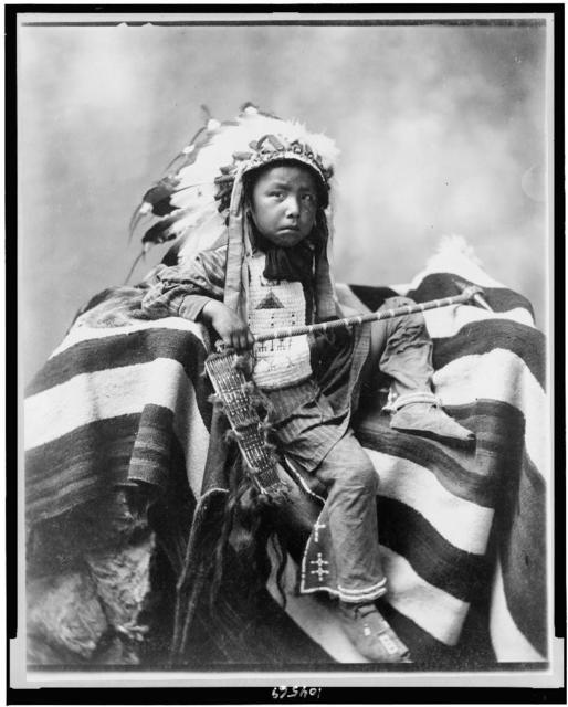 [Joseph Bird Head, Lakota or Sioux, full-length portrait, seated on blanket holding handcrafted club, facing slightly right]