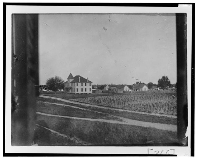 [Large building (residence or meeting house) with outbuildings and cultivated fields]