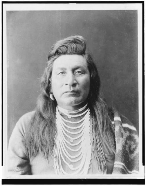 [Nez Percé man, head-and-shoulders portrait, facing front, wearing bead necklace, with blanket over shoulder]