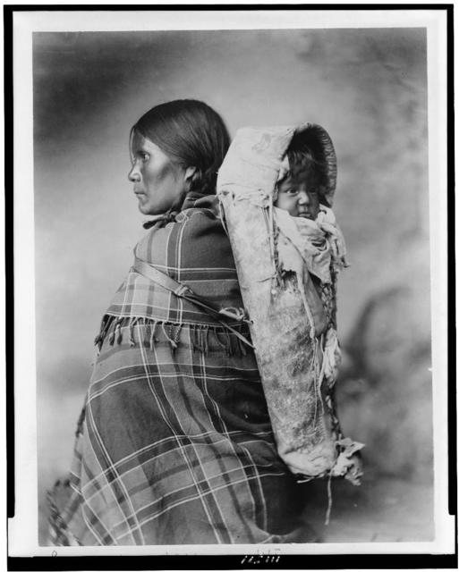 [Pee-a-rat and baby - Utes. Profile of woman, half-length portrait, standing, facing left, in plaid blanket, with baby in cradleboard on her back]