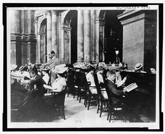 [Students in the Reading Room of the Library of Congress with the Librarian of Congress, Herbert Putnam, watching]