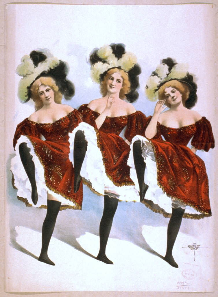 [Three dancing women in red costumes and feathers]