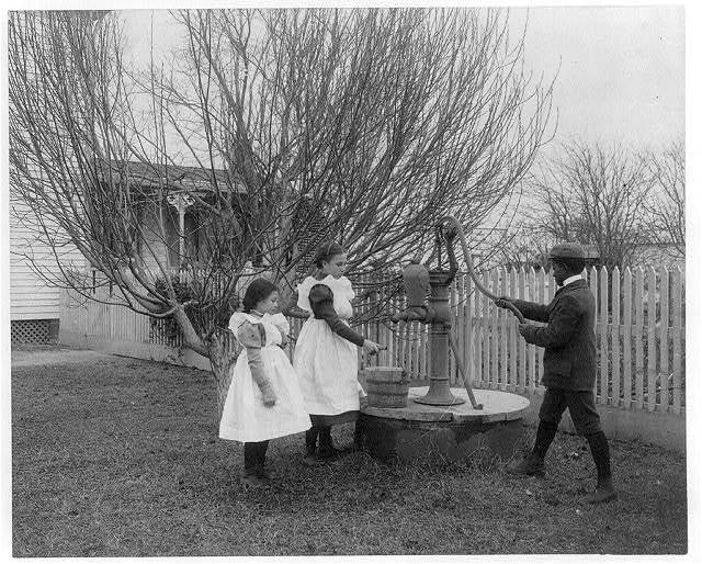 [Two girls and a boy pumping water at well of Hampton Institute graduate]