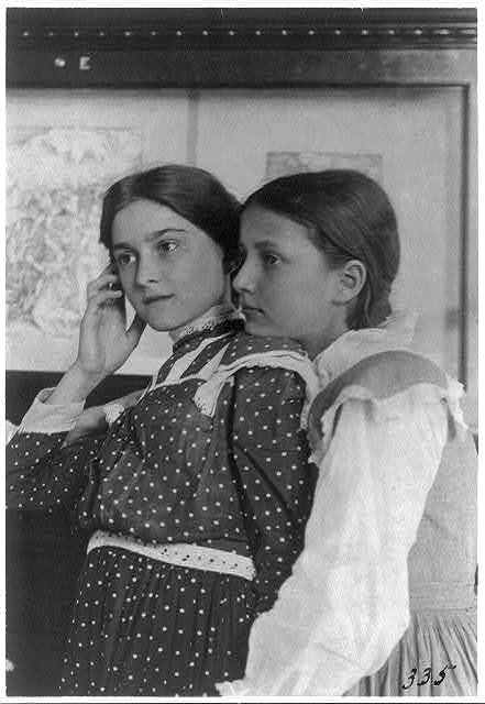 [Two girls from a Washington, D.C., school on a class visit to the Library of Congress, looking at an exhibit of relief or wood engravings, one with her chin on shoulder of the other]