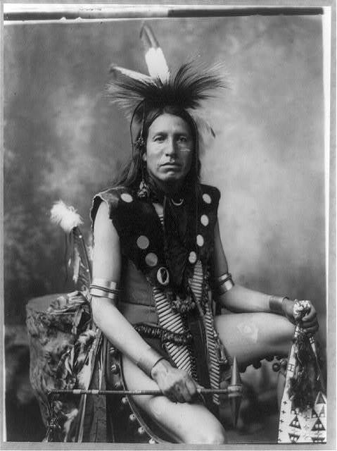 [Yellow Shirt, three-quarter length portrait, seated, facing front; in feather headdress, holding tomahawk]