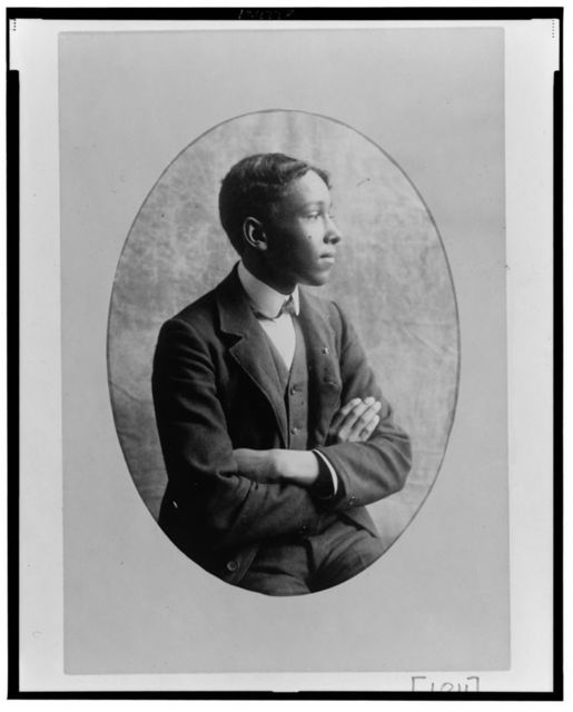 [Young African American man, half-length portrait, seated with arms crossed, right profile]