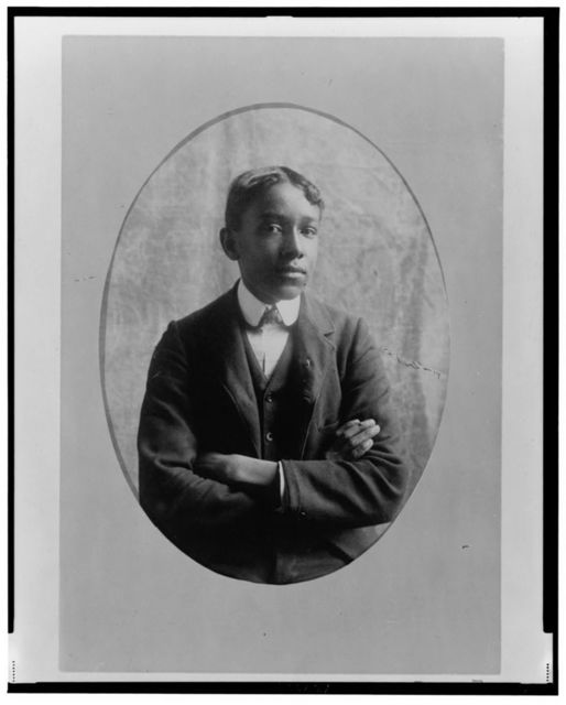 [Young African American man, half-length portrait, with arms crossed, facing front]