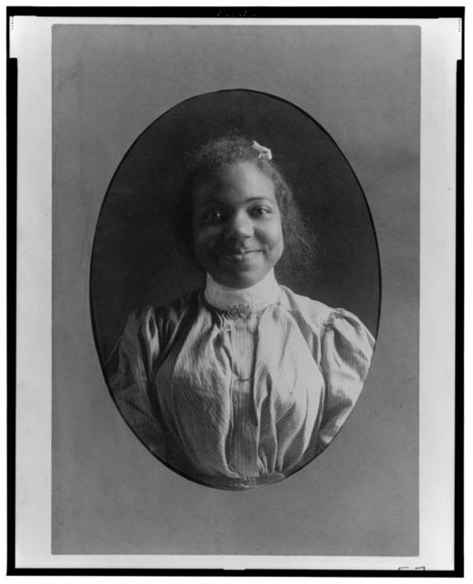 [Young African American woman, half-length portrait, facing front, smiling]
