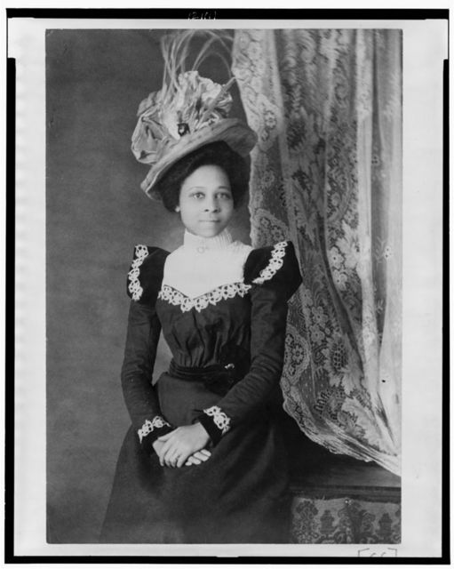 [Young African American woman, three-quarter length portrait, facing slightly right, with hands folded on her lap]