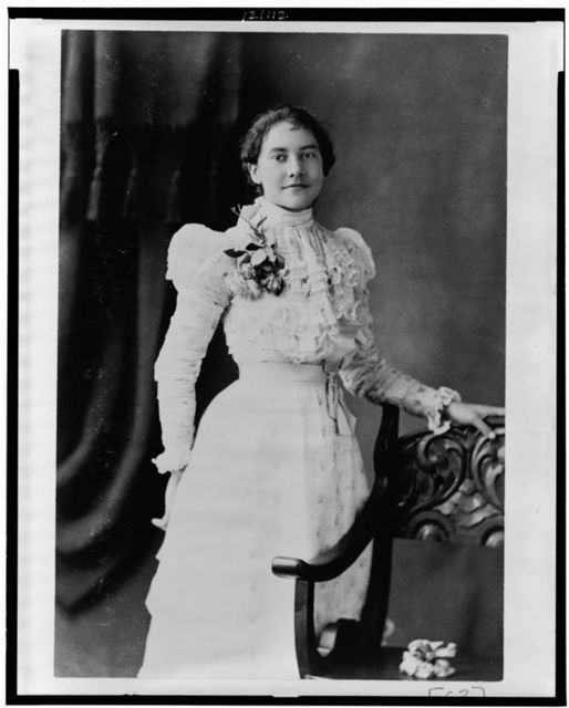 [Young African American woman, three-quarter length portrait, standing, facing slightly right, with left hand on back of chair]