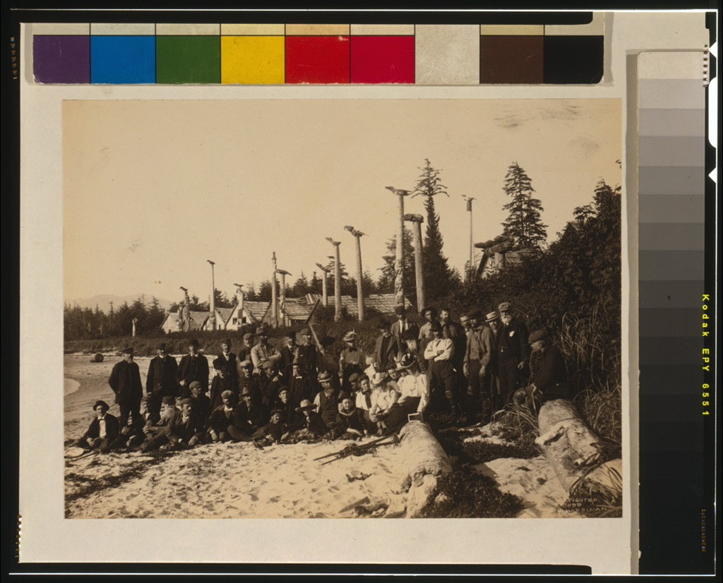 [Harriman Alaska Expedition members pose on beach at deserted Cape Fox village, Alaska, 1899, with Tlinget totem poles in background] / Curtis.