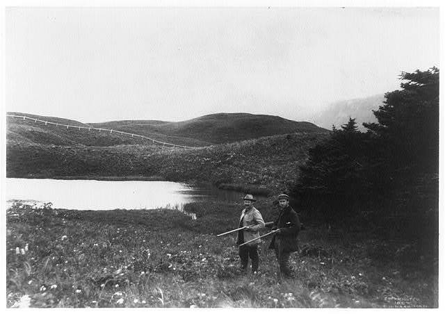 [Two men with guns in foreground, pond and mountain in background, taken during the Harriman Alaska Expedition, 1899]