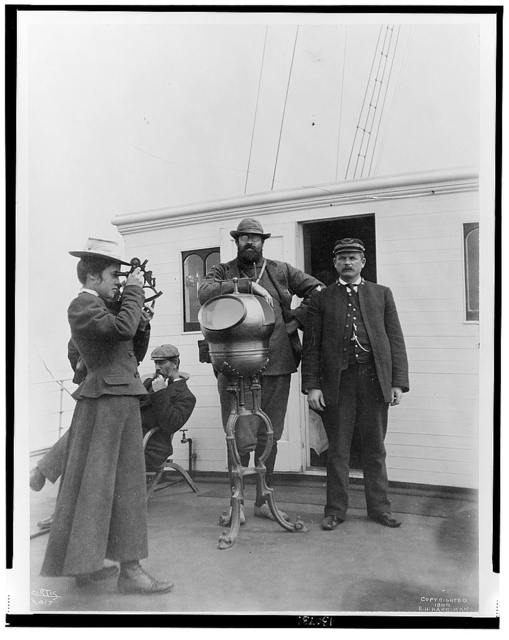 [Woman looking through sextant on board the expedition vessel, George W. Elder, with two men and Capt. Peter Doran during Harriman expedition to Alaska, 1899] / Curtis.