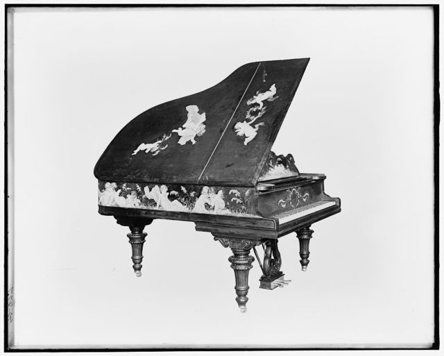 [A Grand piano, cupids on cover]