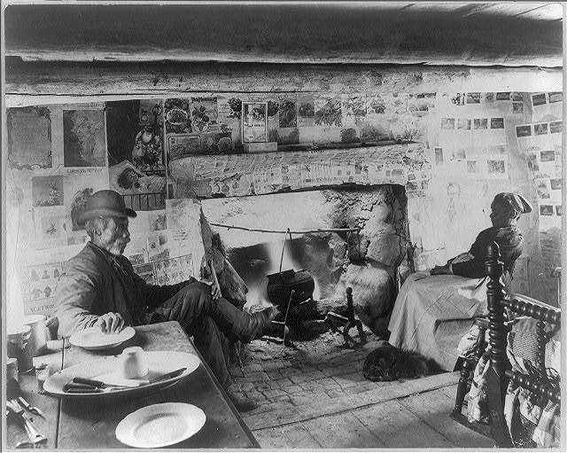 [African American couple sitting in one room cabin near fireplace]